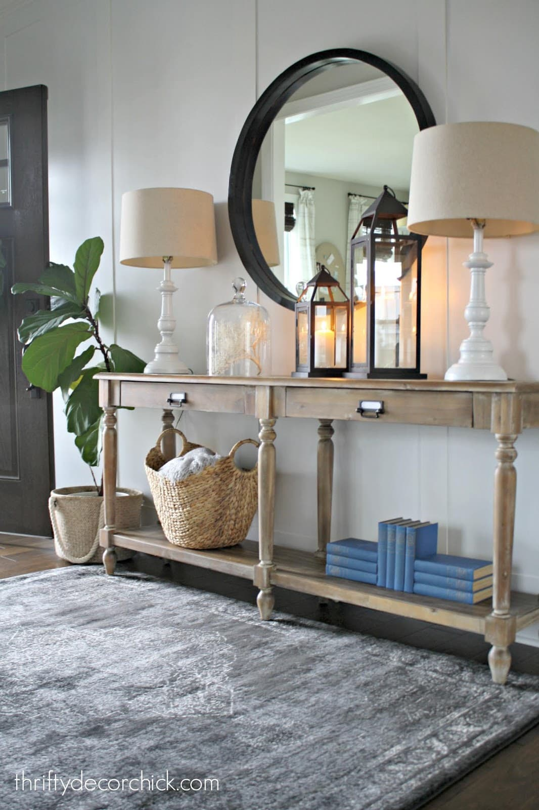 Raw wood entryway console table with large black mirror. The board and batten wall behind it is painted in Agreeable Gray