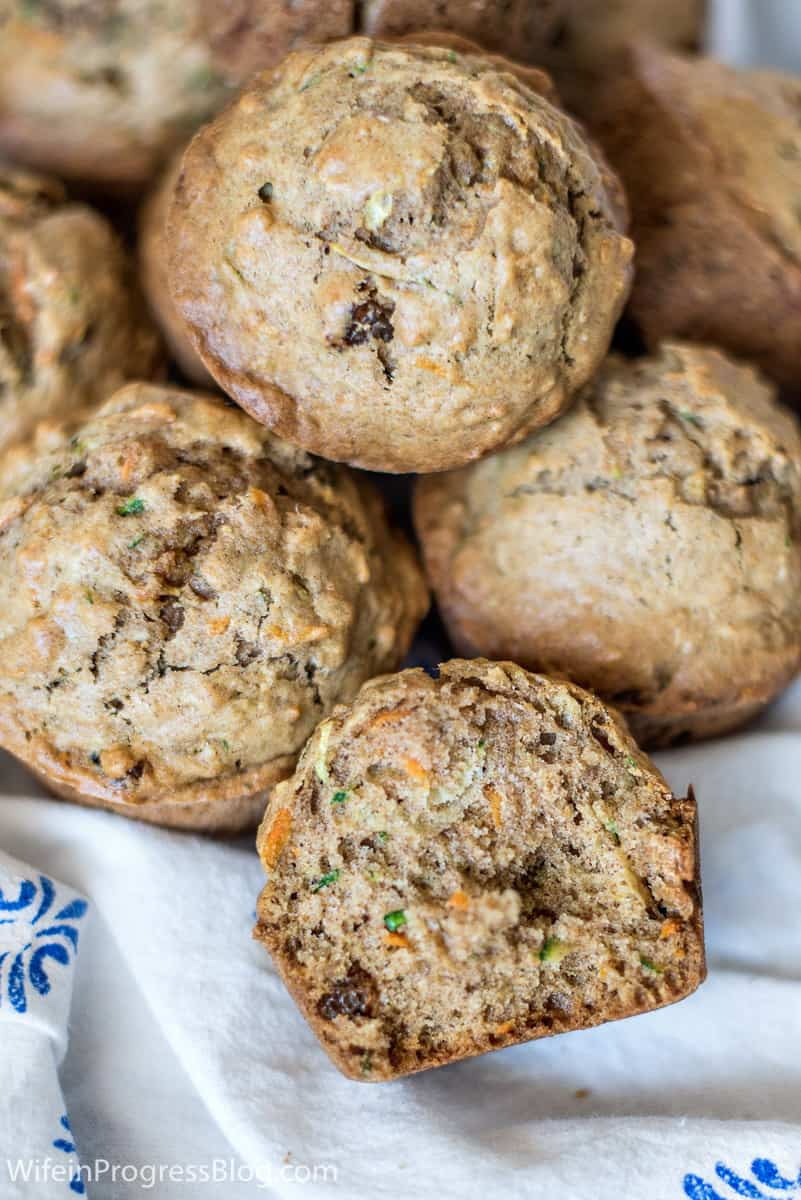 A basket of muffins, with one cut open to reveal the carrot and zucchini inside