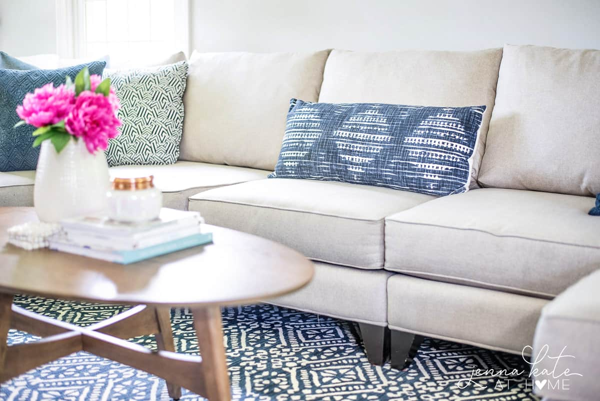 A light grey sofa in the living room with blue patterned pillows and a large blue & white rug
