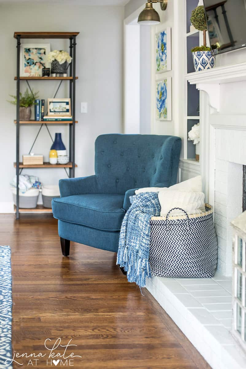 A living room with a tall, blue chair, a container of pillows and throws and a 4-tier shelf in the background with various decor items