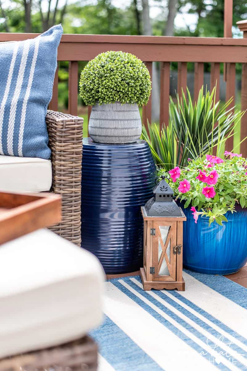 Decorating your outdoor spaces with plants, tables, and rugs is a great way to make outdoor entertaining spaces more comfortable!