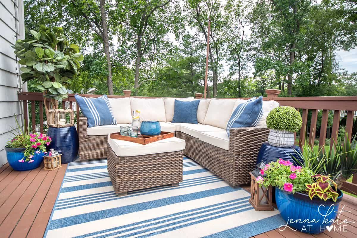 Restored wooden deck with brown & beige outdoor furniture and blue elements (pillows, plant pots etc).