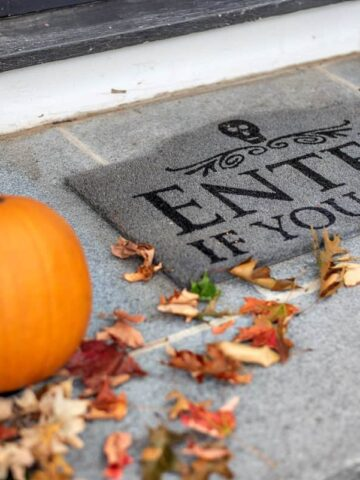 """A grey, outdoor welcome mat with the words """"Enter if you dare"""" with 2 orange pumpkins and a scattering of fall leaves nearby"""