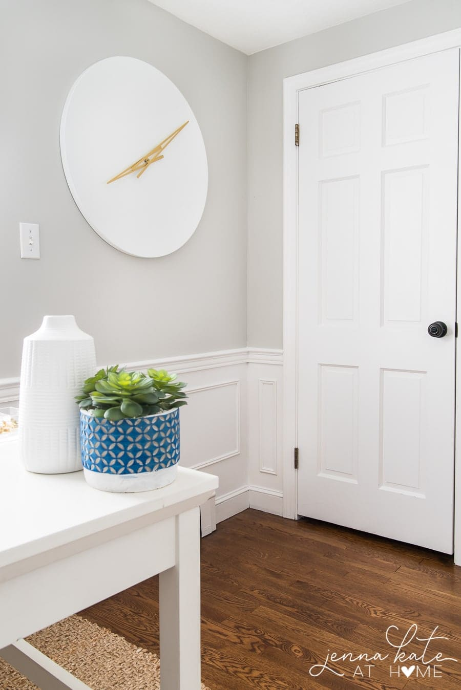 The edge of a desk, holding a potted plant and tall, white jug, with a large, white clock with gold handles nearby, and the door in the background