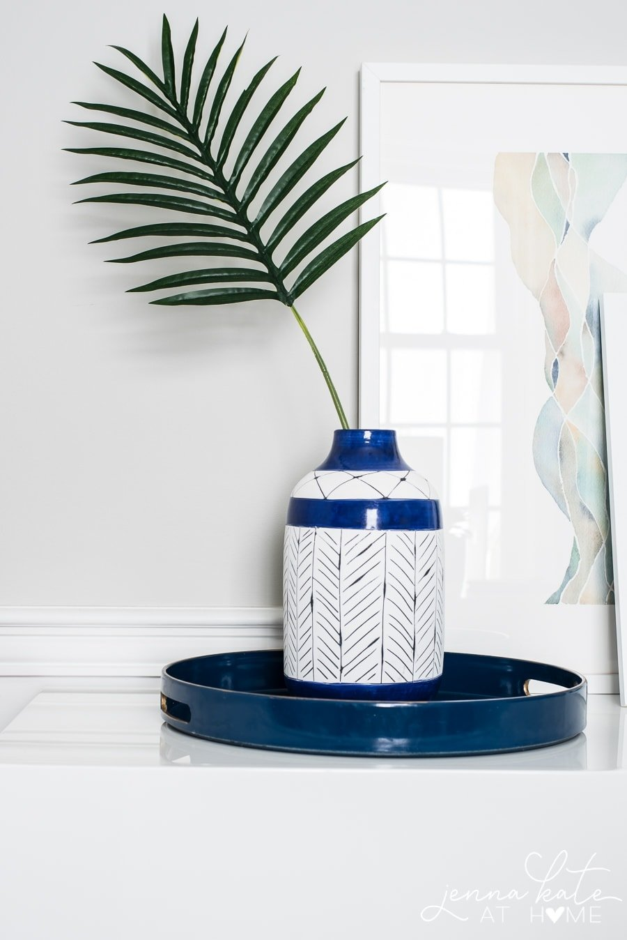 A white jug with painted dark blue line patterns, resting on a circular blue tray, holding a single palm frond near large framed art
