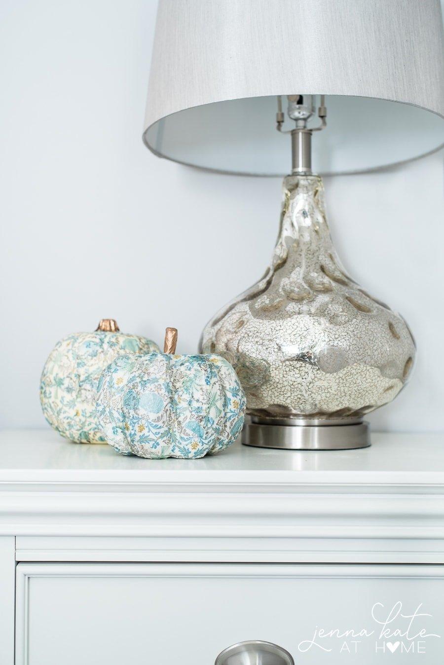 decoupaged pumpkins next to a mercury glass lamp