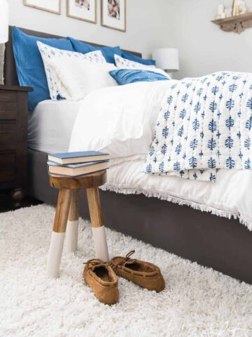 A made bed in a room with a stool and slippers next to it