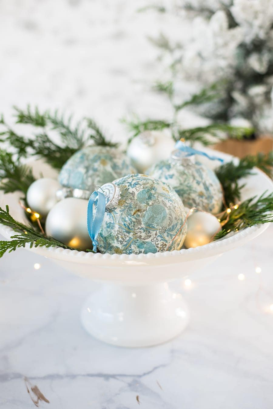 A white pedestal bowl with a beaded trim, holding blue and silver ornaments and sprigs of pine
