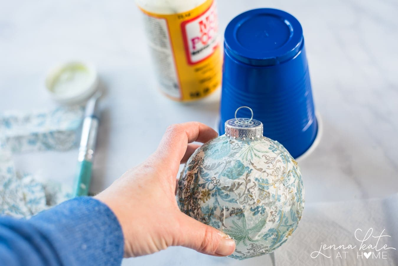Jenna holding the ornament, now fully dry and covered with the blue napkin; blue cup, Mod Podge and paint brush in the background