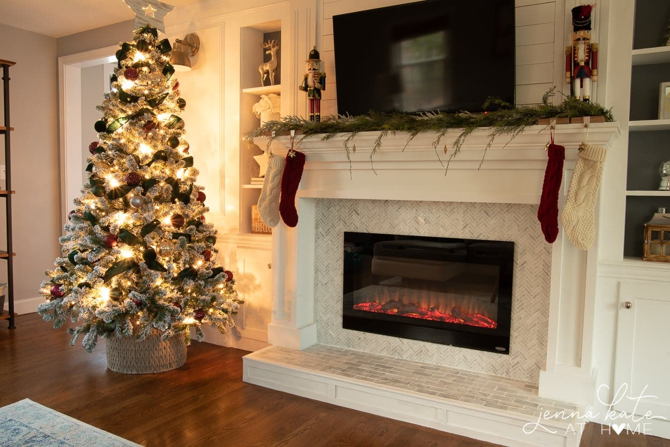 A Christmas tree in a dark room, lighted, near a fireplace holding stockings and various holiday decor