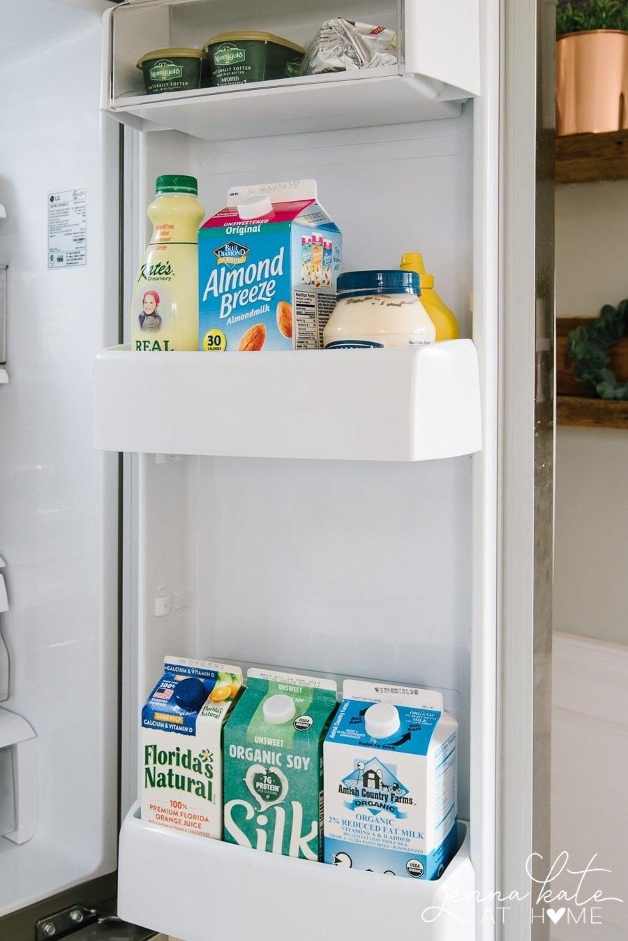 The door of a refrigerator holding various jugs of milk and orange juice
