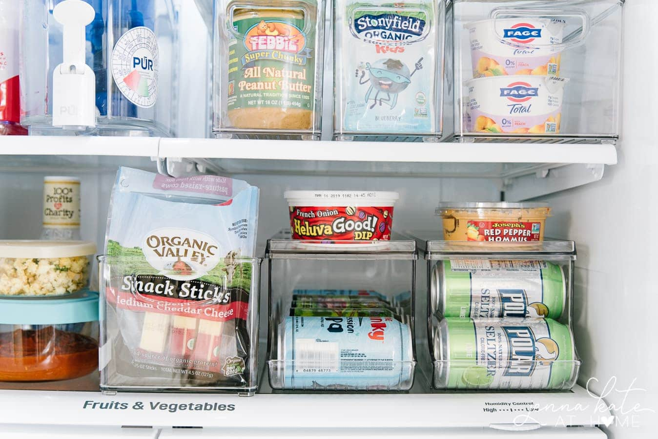 An open refrigerator with plastic organizers to hold cans of beverages, cheese snacks, yogurt and bottles of water