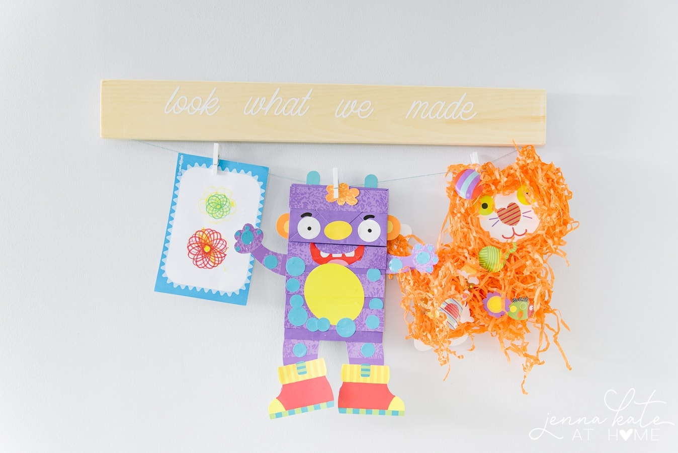 """A wooden artwork hanger with the words \""""Look what we made\"""", and a clothes line and pegs holding colorful artwork"""