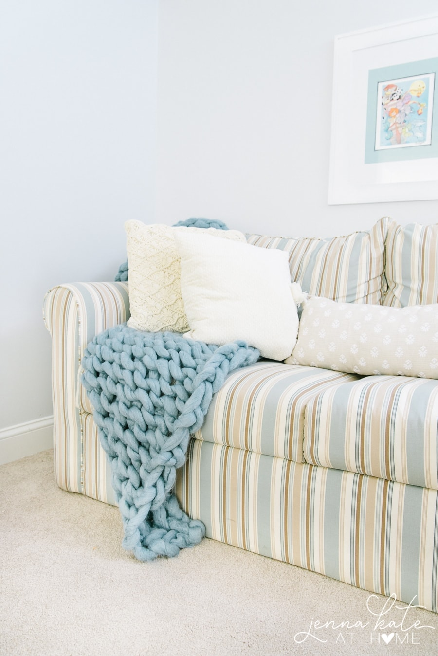 A beige and blue striped sofa, with beige throw pillows and a thick blue blanket
