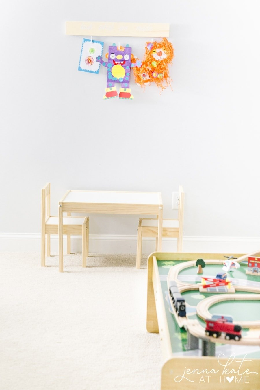 A child\'s playroom with a small table and two chairs, a wooden train table and various artwork hanging on a wooden display