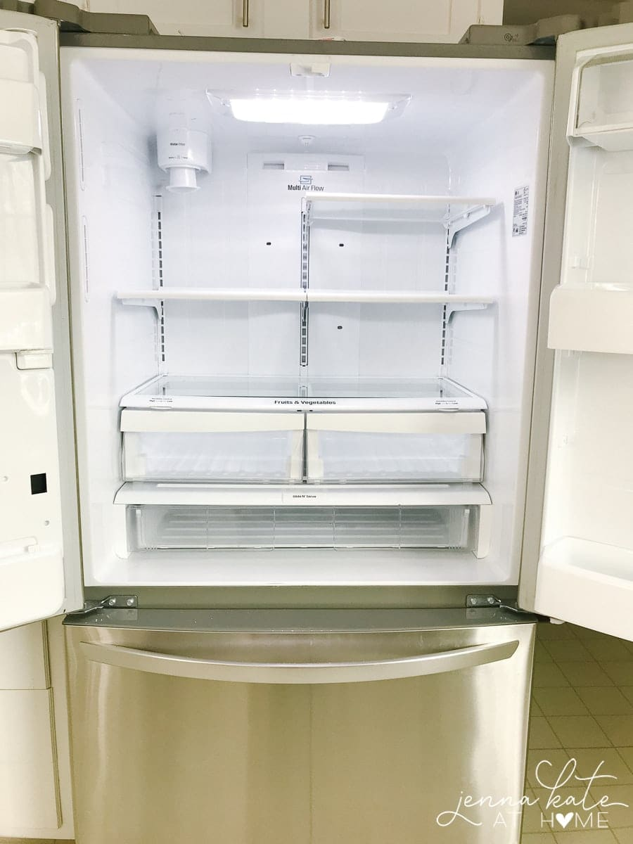 An open refrigerator with empty shelves and drawers