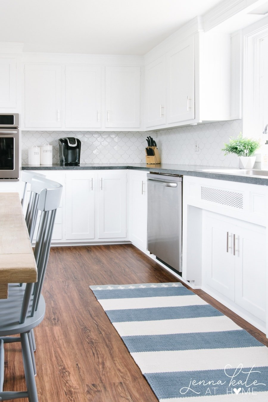 white kitchen with dark wood floors and a blue and white striped area rug