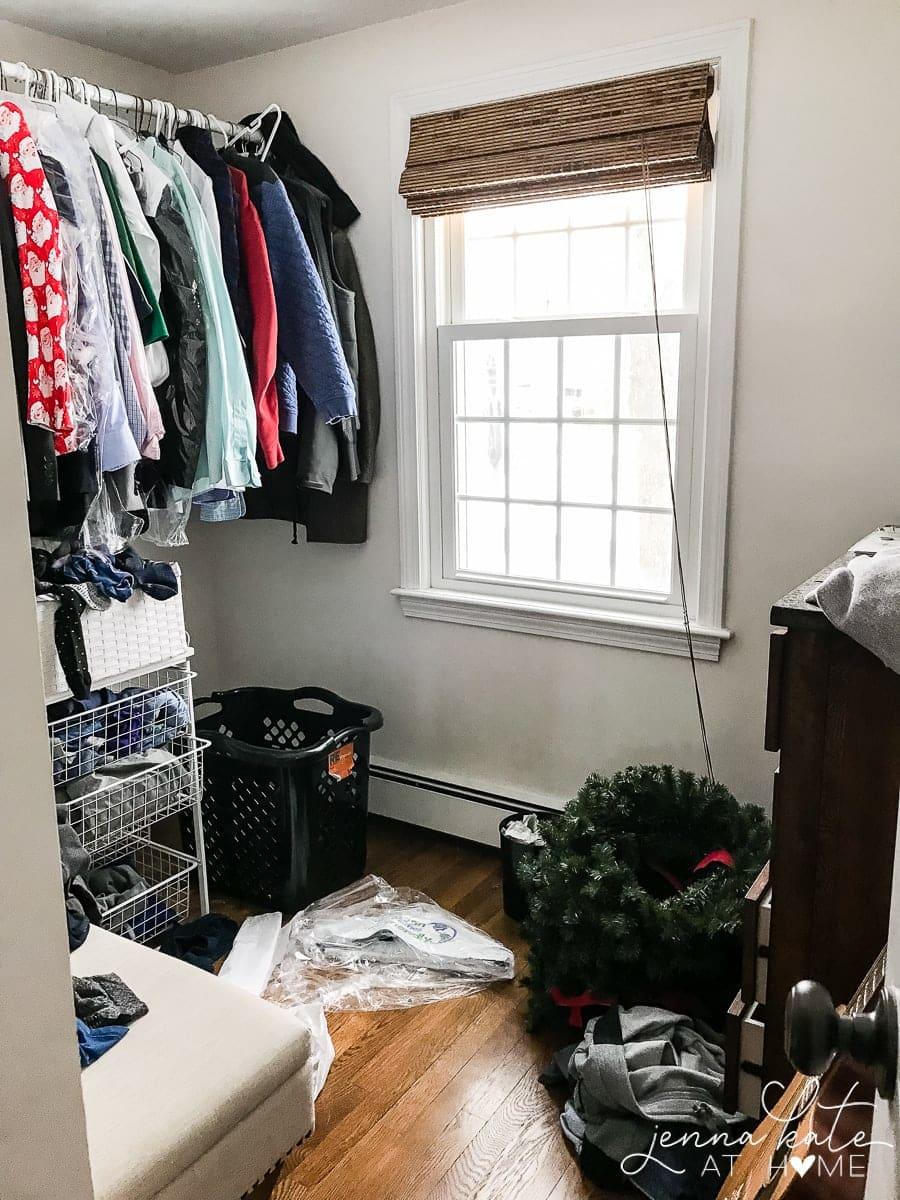 Clothes hanging on a rod near a window, above a wire rack of other clothing, with miscellaneous items resting nearby