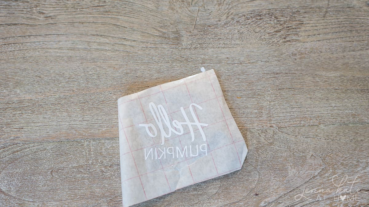 Reverse side of vinyl patch with white lettering, resting on wooden table