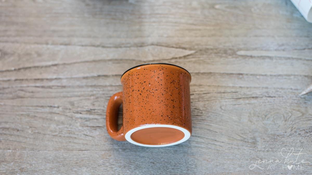 Plain, ceramic mug awaiting transfer of vinyl lettering
