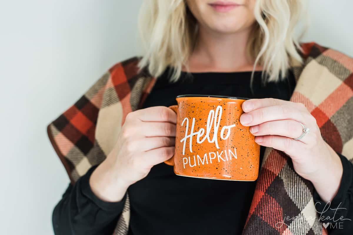 "Author, wearing seasonal fall wrap, holding finished DIY mug with vinyl lettering ""Hello Pumpkin"""