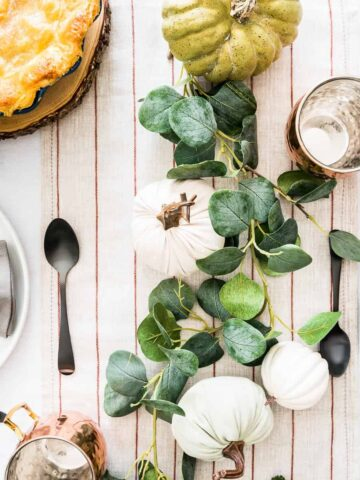 table filled with plates, cutlery, apple pie and fall decorations