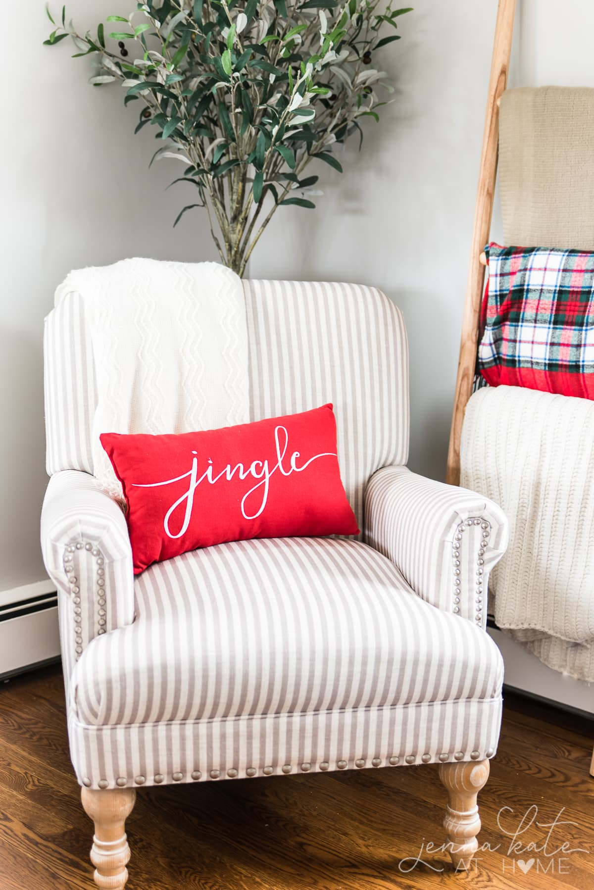 """Arm chair in the corner of a room with a red pillow that reads \""""jingle\"""""""