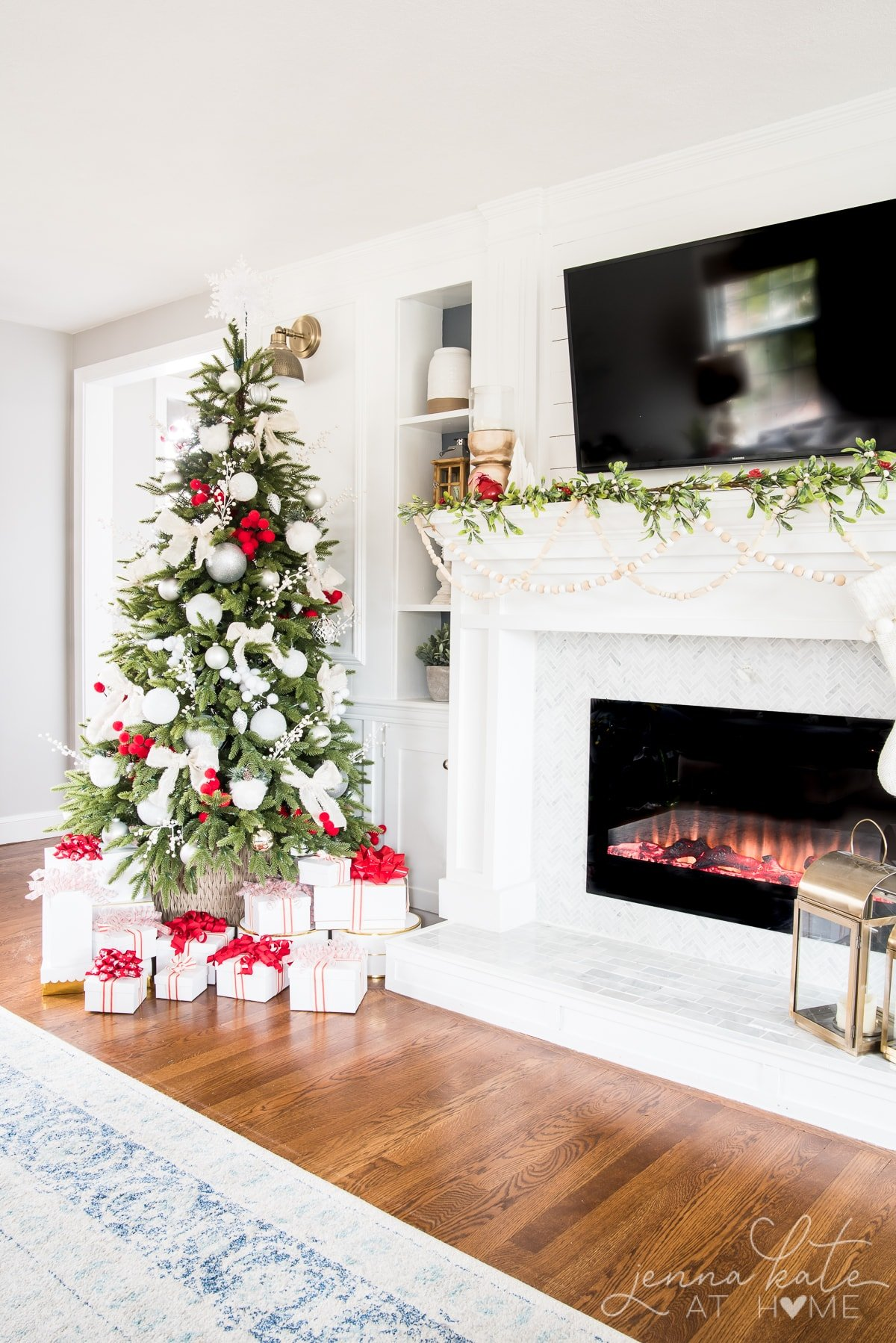 Living room fireplace mantel and Christmas tree decorated in shades of white and red
