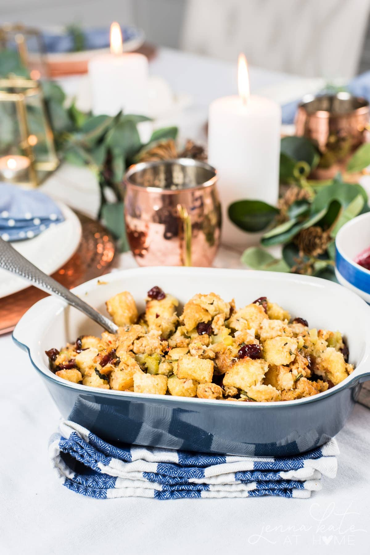 Traditional stuffing in a bowl around Thanksgiving table setting