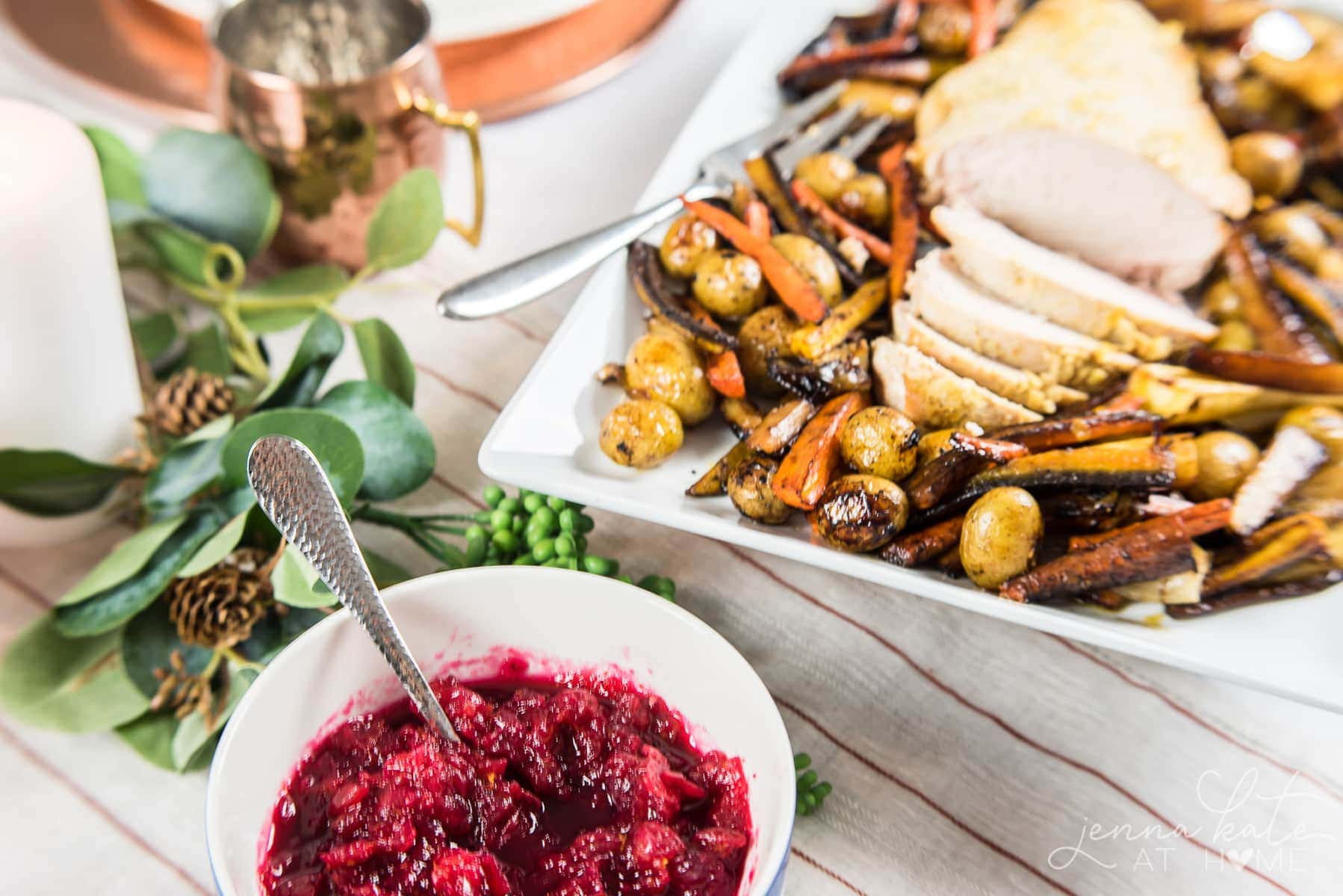 A tender, juicy roasted turkey breast served over tender roasted carrots and potatoes and homemade cranberry sauce