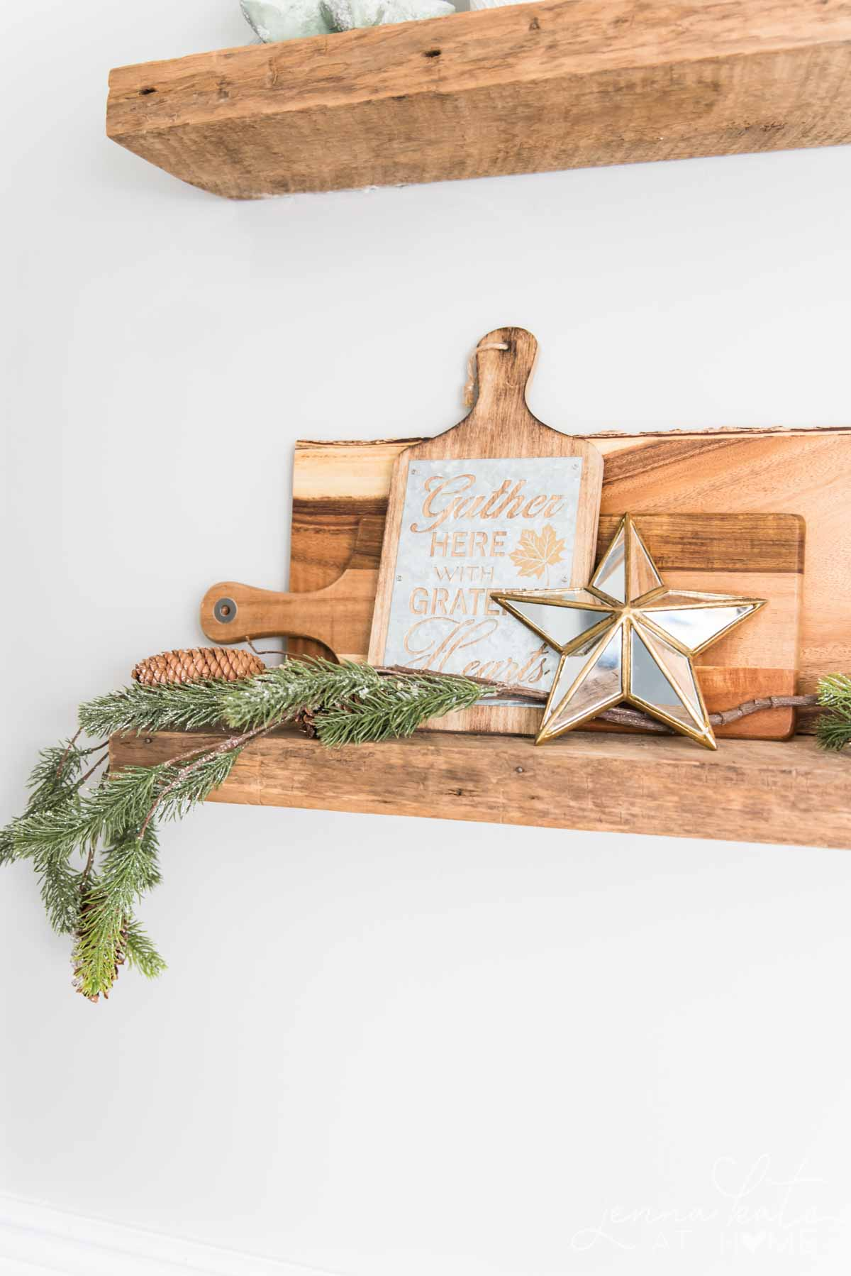Kitchen shelves with Christmas decor, wooden cutting boards and greenery