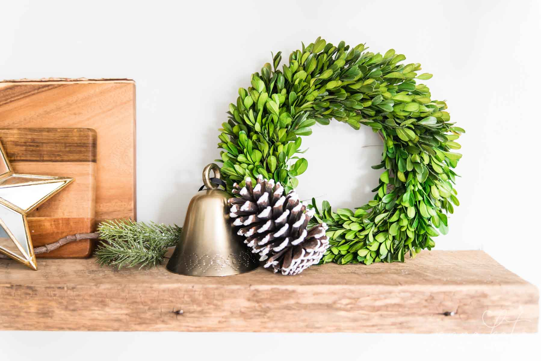 Small boxwood wreath, bell and a large pinecone