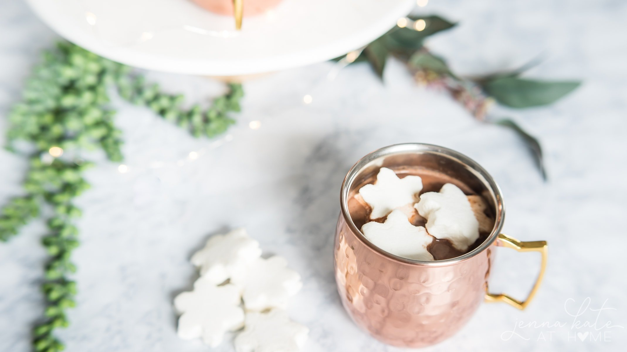 creamy hot chocolate in a copper mug with snowflake marshmallows