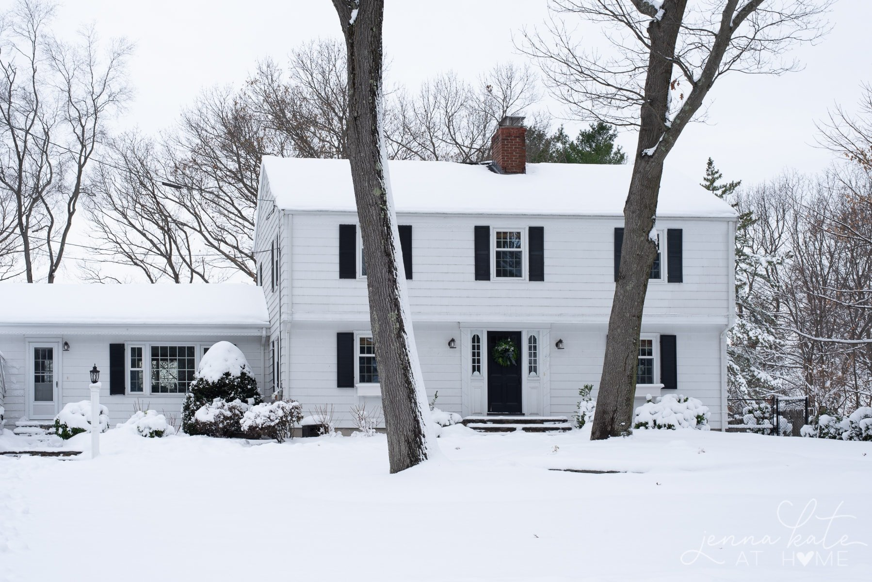 White Colonial house covered in snow