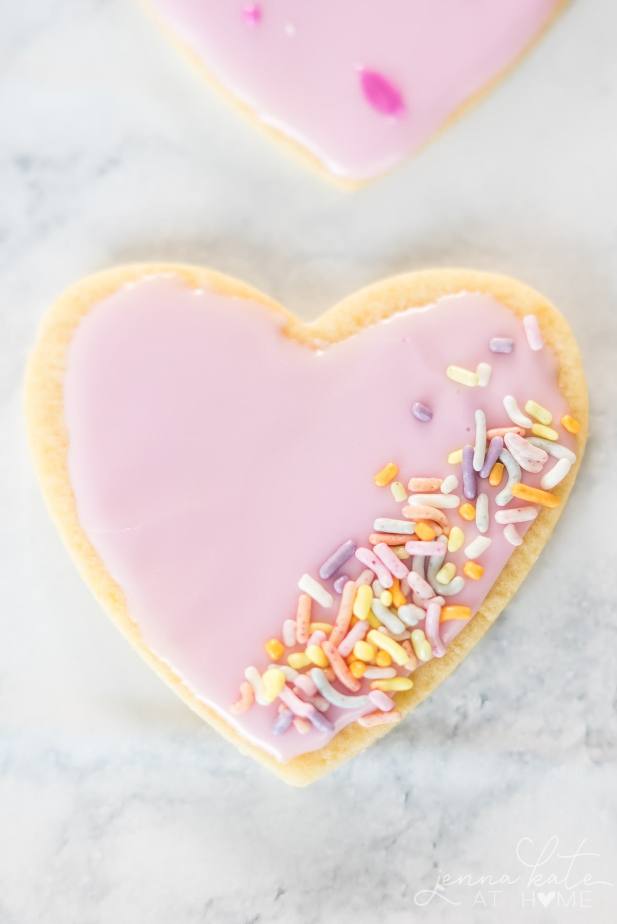 Close up of Valentine heart sugar cookie with pink frosting and sprinkles