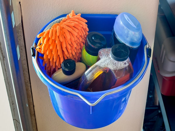 Car cleaning supplies in bucket hanging from garage wall
