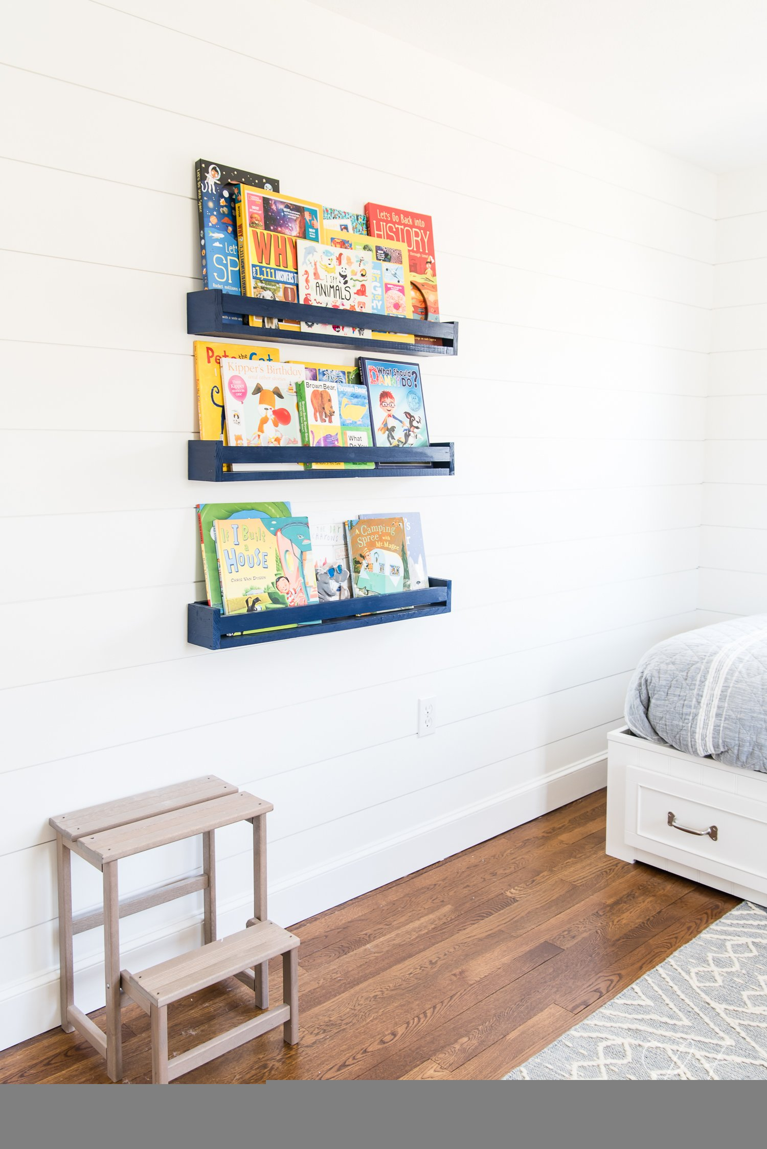 DIY book navy blue book ledges filled with kid's books form part of the decor
