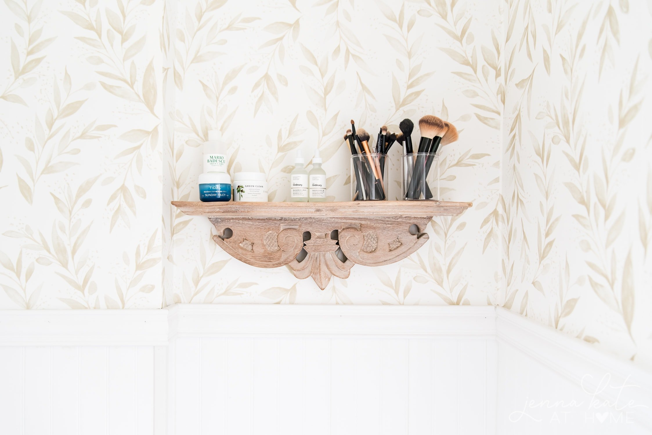 natural wood bathroom shelf with skincare products and makeup brushes