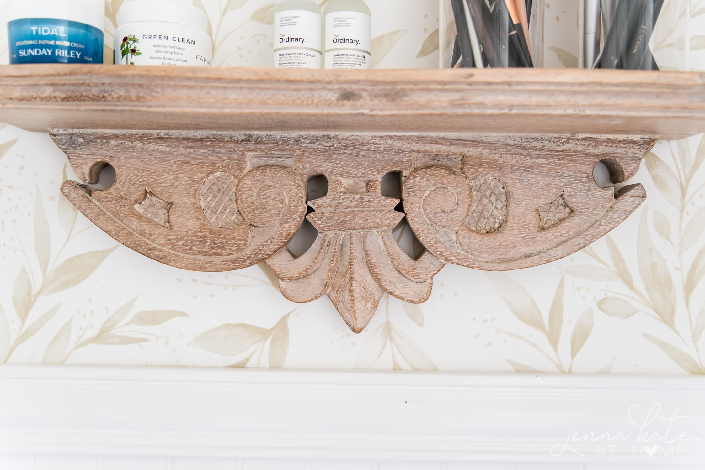 Closeup of carved details on the natural wood bathroom shelf