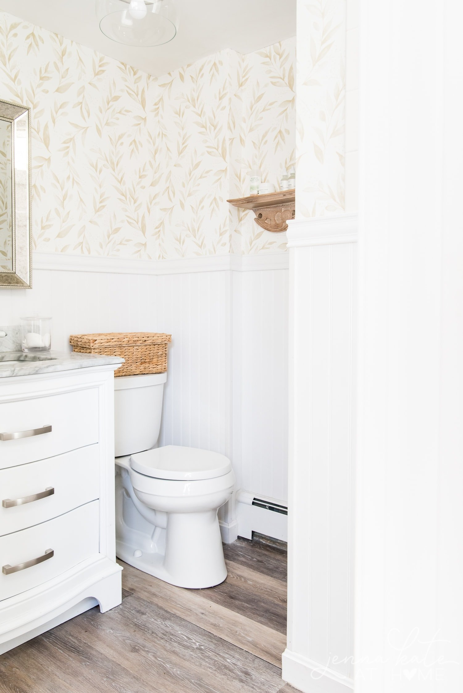 View of bathroom from another angle. Here you can see the toilet with wicker basket on top as well as the beadboard and wallpaper on the walls.