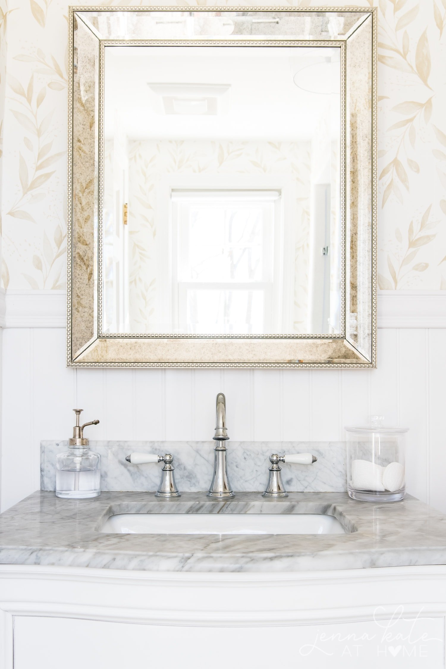 Reflection of bathroom in the mirror over the marble topped vanity with chrome faucets.