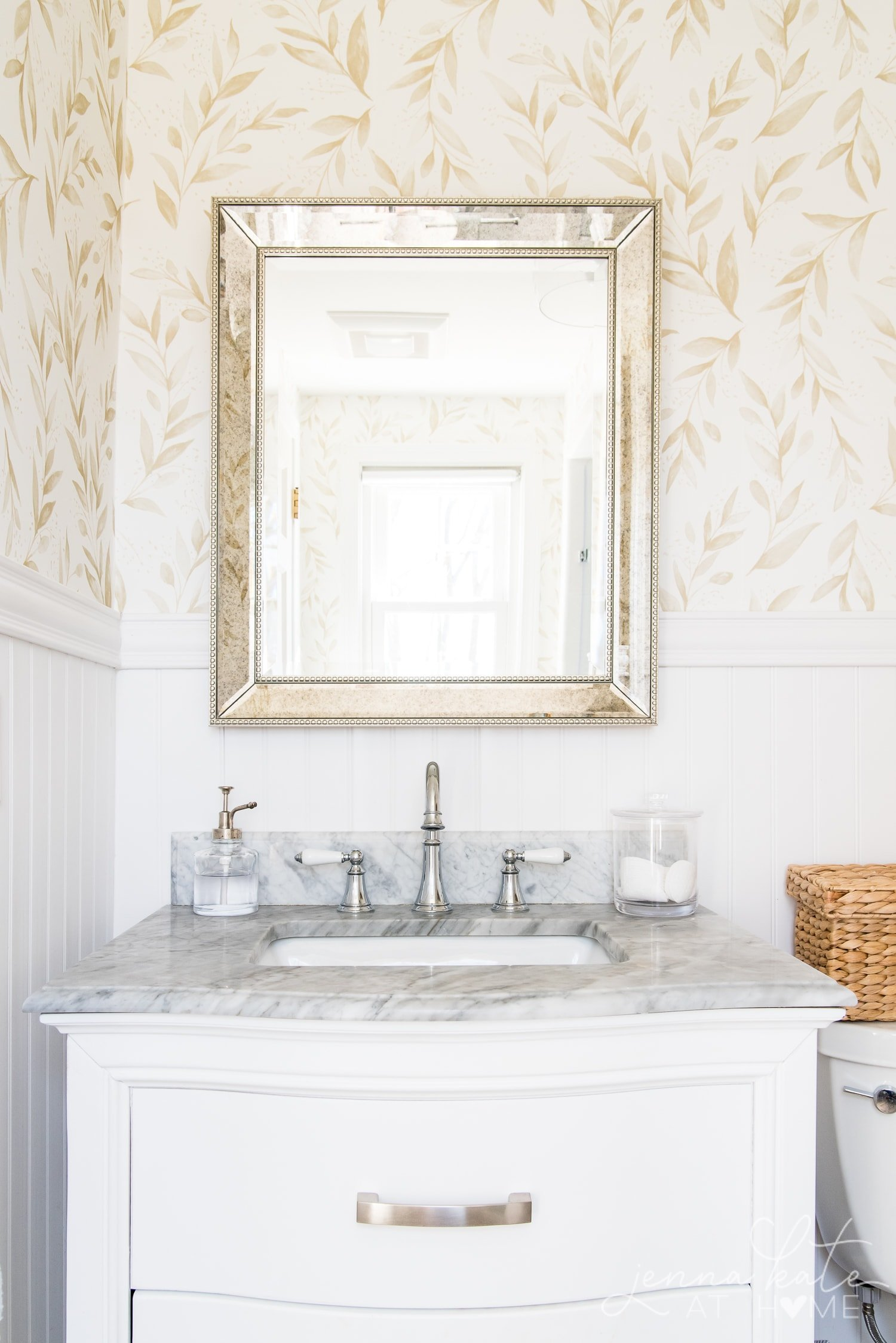 Elegant bathroom with floral wallpaper, chrome hardware and white vanity