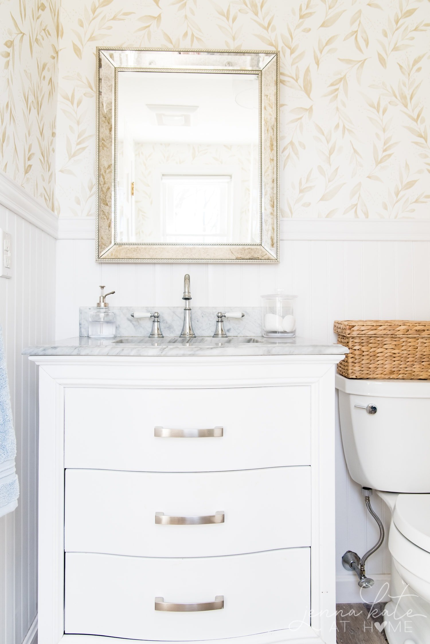 White vanity and marble top with a mercury glass mirror overhead showcasing the elegant floral bathroom wallpaper