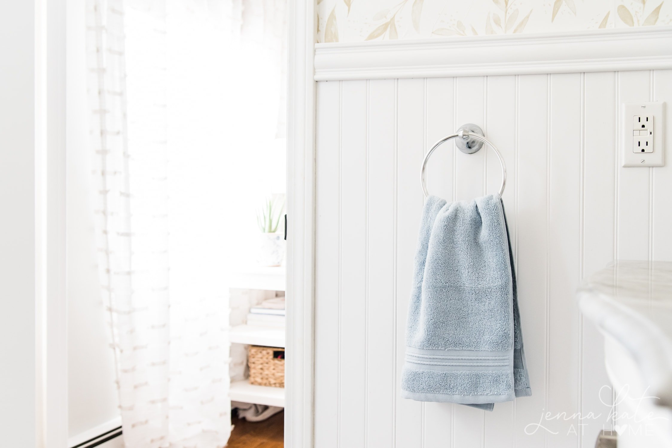 Powder blue towel hanging against white bead board in master bathroom