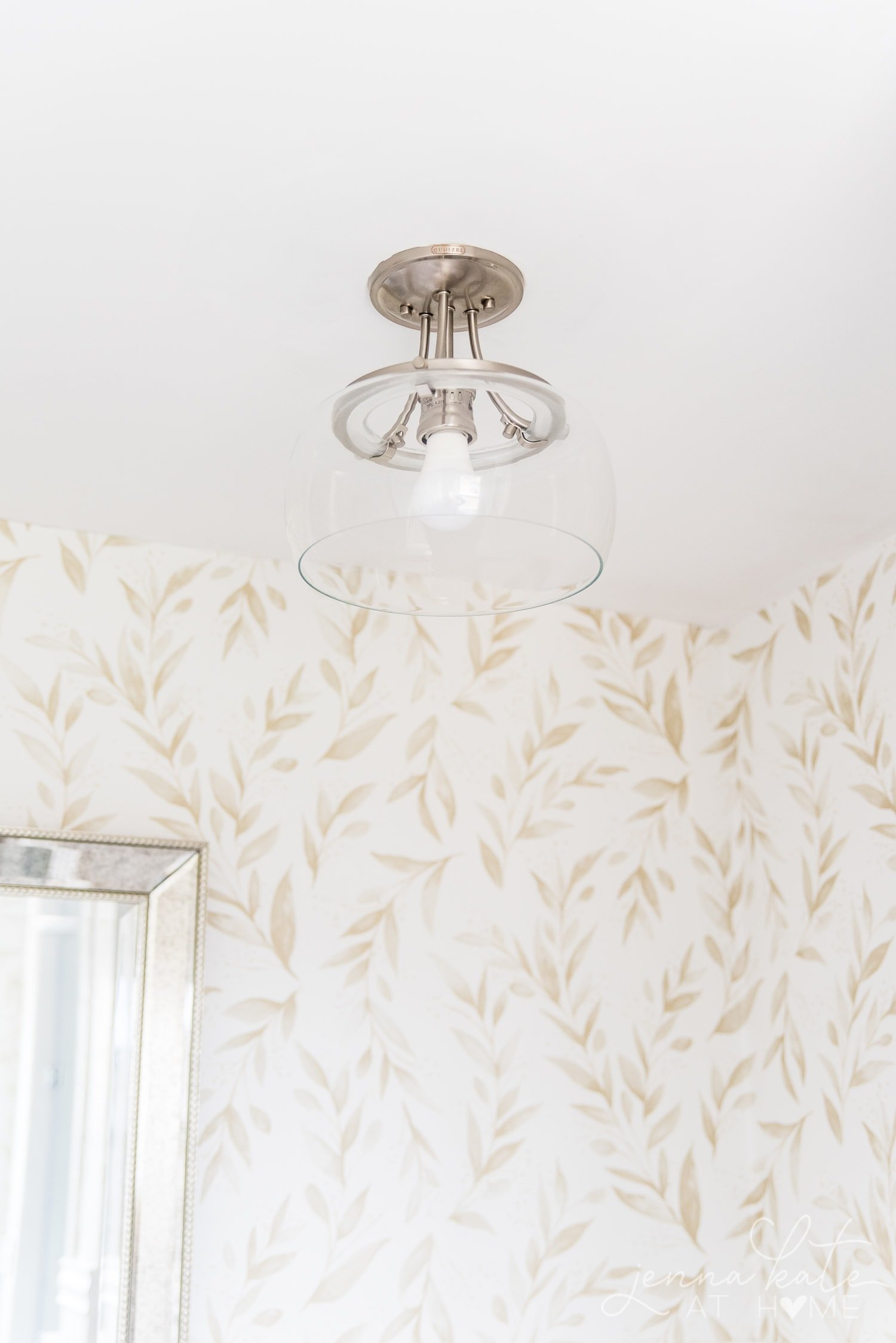 Clear glass light fixture against backdrop of new wallpaper