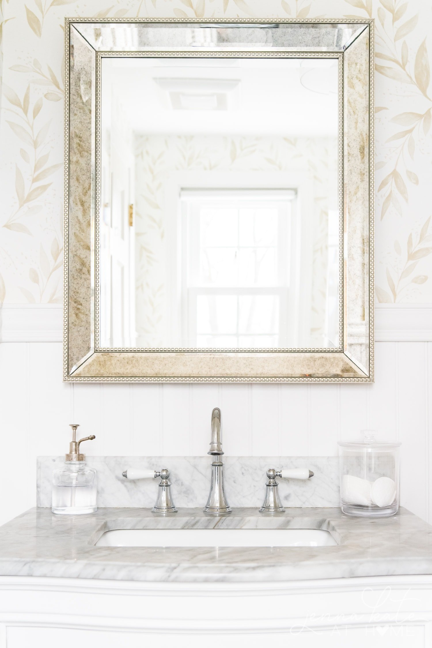 Mercury glass mirror reflecting beautiful floral wallpaper in bathroom
