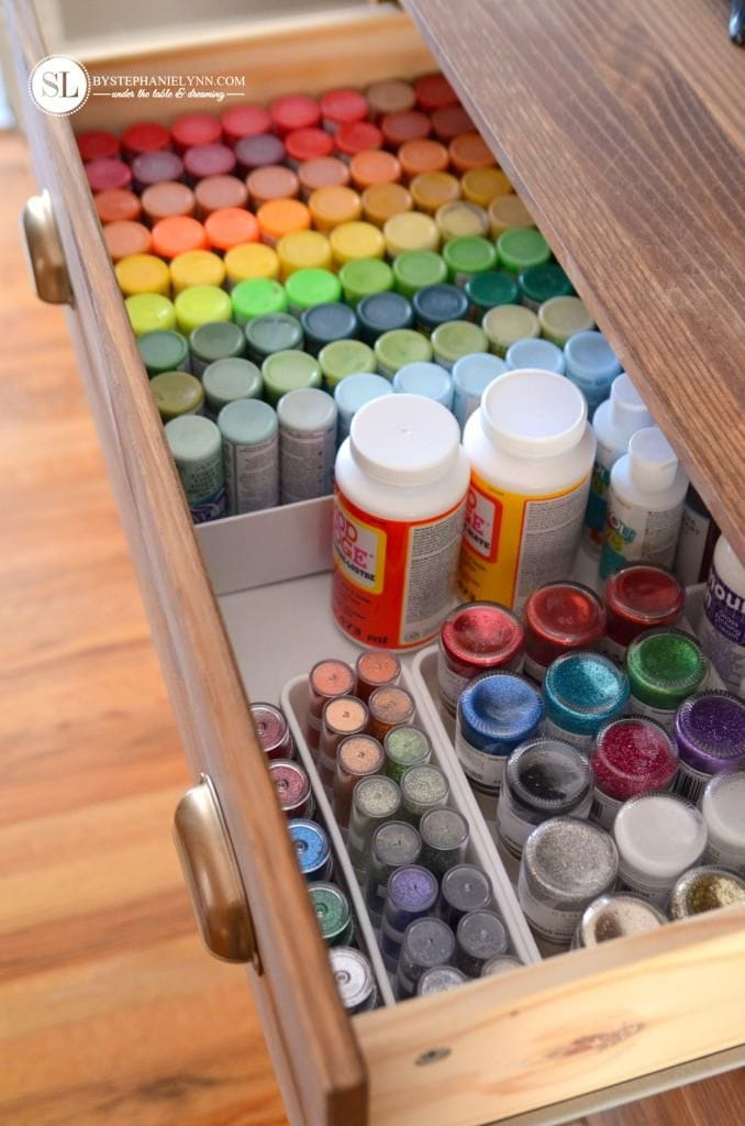 Craft room drawer organized with paint, glue and glitter supplies