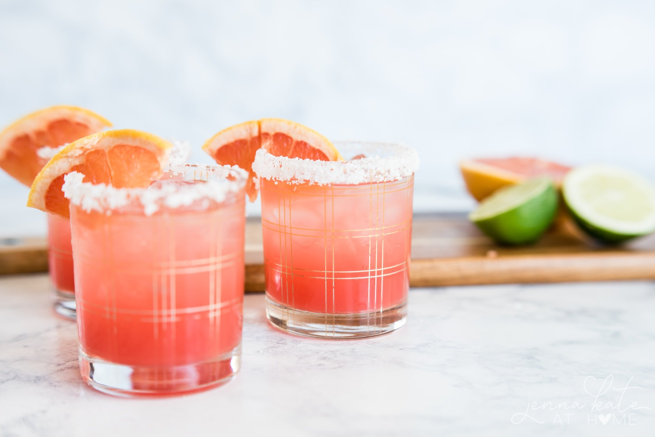 Three graprefruit cocktails with limes in the background