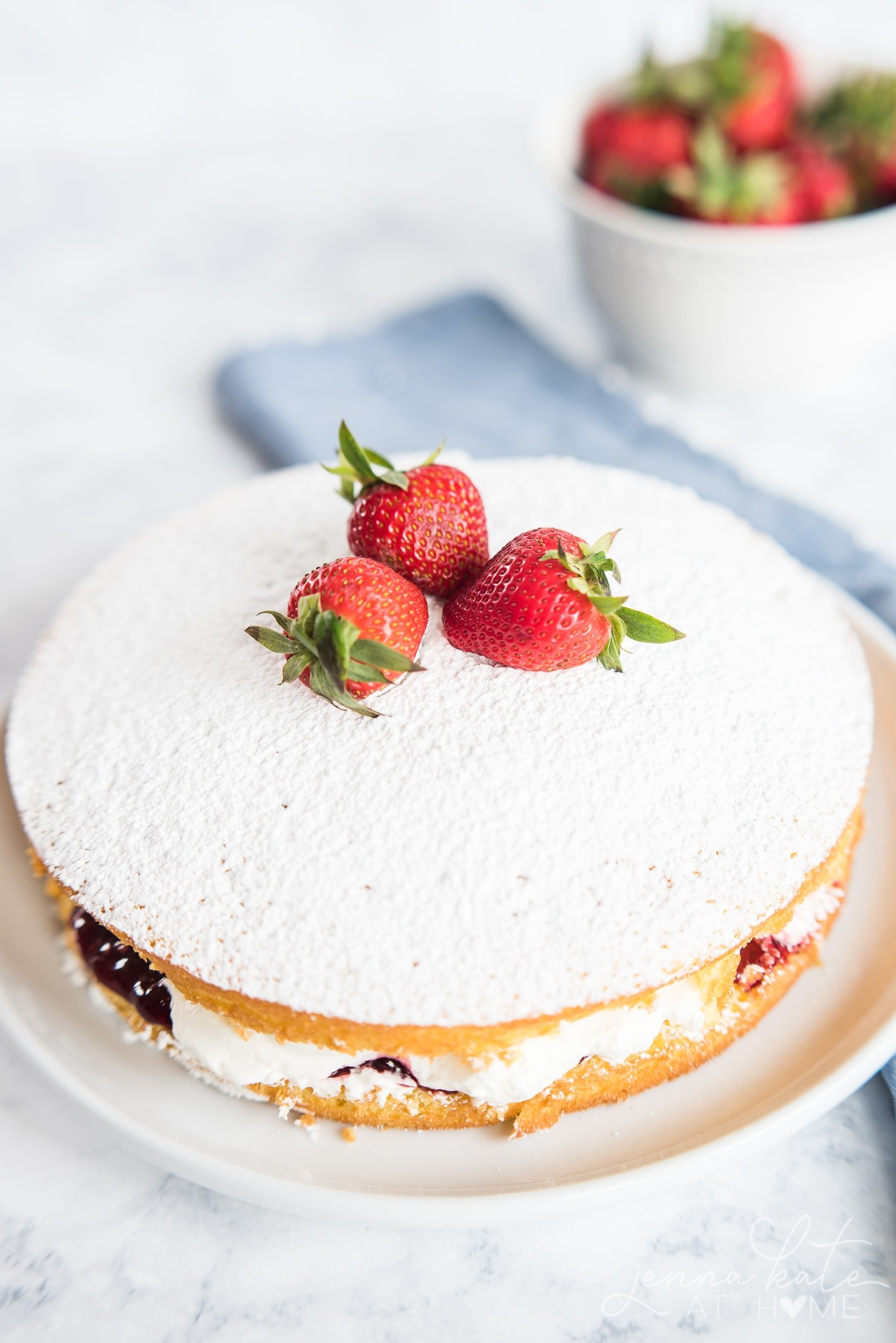 Top of victoria sponge cake, dusted with powdered sugar with 3 strawberries in the center