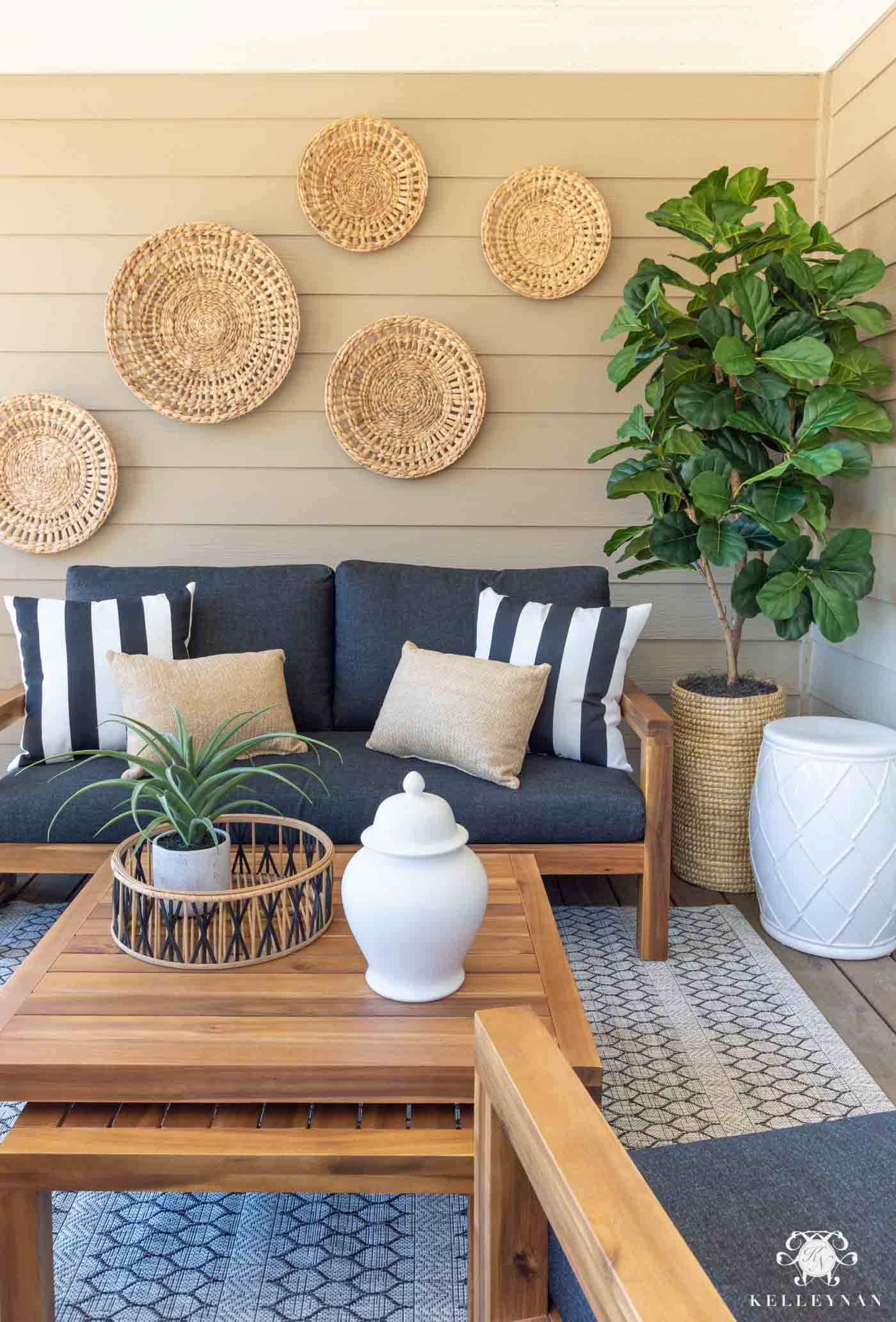 Simple porch decor with gray couch and baskets hanging on the house's siding
